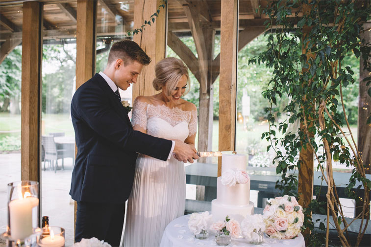 Bride and groom cutting the cake - three tier wedding cake adorned with ivory sugar flower #weddingcake