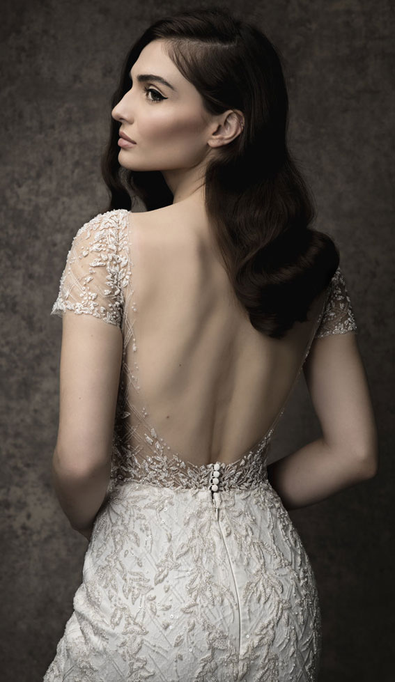 Scooped neckline with illusion short sleeves and deep scooped illusion back, on a fitted trumpet silhouette. Fully lined with Chantilly lace and Ivory beading throughout. Enaura 2019 Wedding Dresses #weddingdress #wedding wedding gown