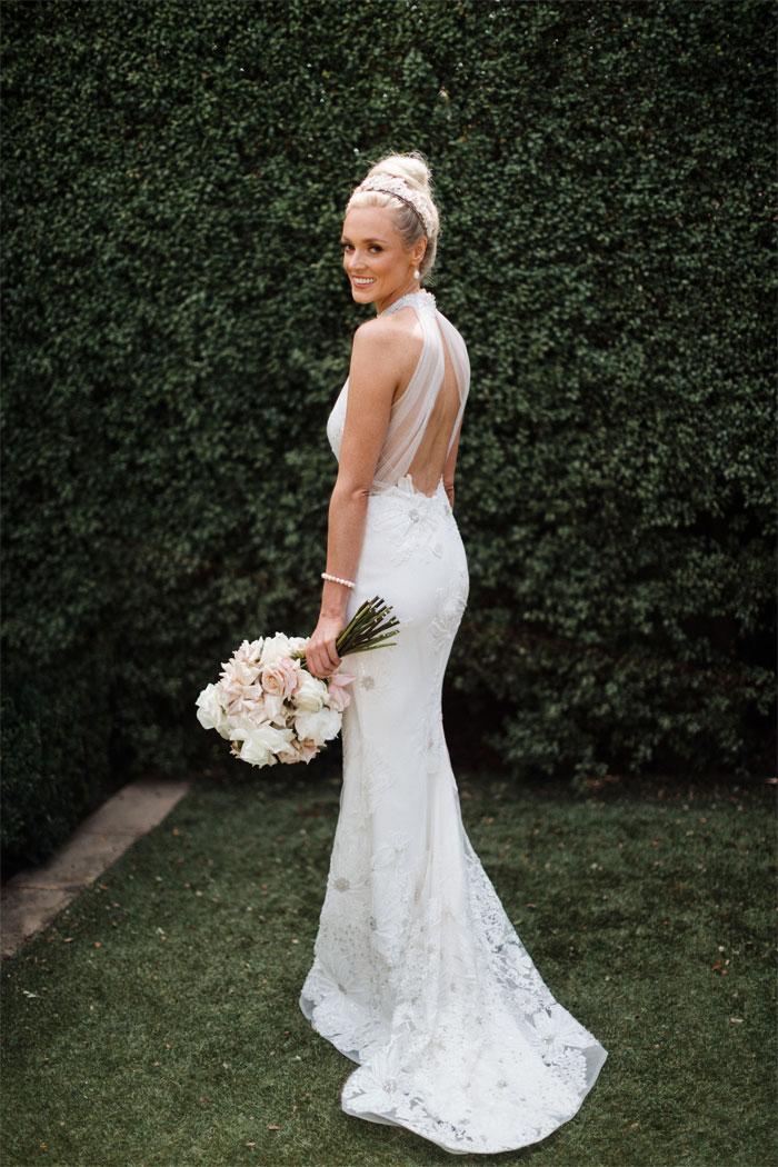 stunning bride with pale pink bouquet wears halter neck wedding dress